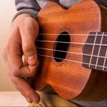 Closeup of young man hands playing concert ukulele